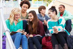 High School Students Sitting Outside Building With Phones Stock Photo
