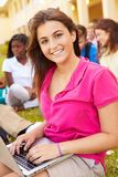 High School Students Studying Outdoors On Campus. With Female Teenager Using Laptop Smiling Stock Image
