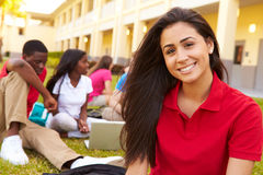 High School Students Studying Outdoors On Campus. Sitting Down Using Laptop With Teenage Girl Smiling At Camera Stock Image