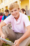 High School Students Studying Outdoors On Campus. With Teenage Boy Smiling At Camera Holding Digital Tablet Stock Images