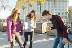 High school students are talking outdoor. Girl teenager showing on a clean white sheet in notebook and boy looking at notebook stock images