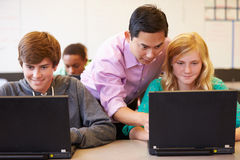 High School Students With Teacher In Class Using Laptops Stock Photo