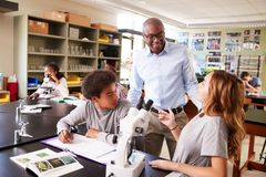 High School Students With Tutor Using Microscope In Biology Class royalty free stock photo