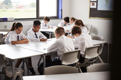 High School Students Wearing Uniform Sitting And Working Around Table In Lesson stock photography