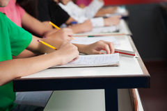 High School Students Writing On Paper At Desk. Midsection of high school students writing on paper at desk in classroom Stock Photos