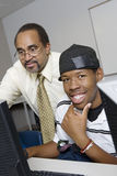 High School Teacher Helping Student. Portrait of happy male student with professor in computer lab Stock Image