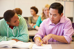 High School Teacher Helping Student With Written Work Stock Photos