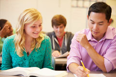 High School Teacher Helping Student With Written Work Royalty Free Stock Photos