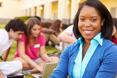High School Teacher Sitting Outdoors With Students On Campus. Looking At Camera Smiling Stock Photo