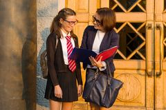 High school teacher is talking to female student near the front door of the school Stock Photos