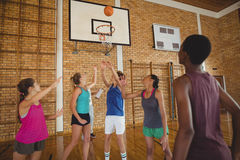 High school team scoring a goal while playing basketball. In the court Stock Photography