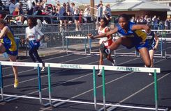 High school teens participate in a hurdle event. In a track and field event royalty free stock photography