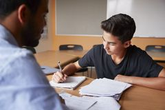 High School Tutor Giving Male Student One To One Tuition At Desk royalty free stock photos