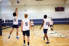 High School Volleyball Match In Gymnasium. With Boy Throwing The Ball In The Air royalty free stock images