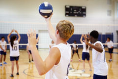 High School Volleyball Match In Gymnasium. With Young Boy Holding Ball In The Air royalty free stock photography