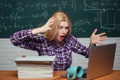 High school. Young teacher near chalkboard in school classroom. Tired student. Student sitting at table and writing on. Notebook. Bored student doing homework stock image