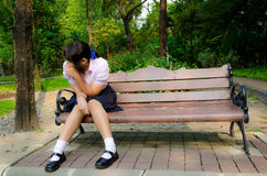 High-Schoolgirl crying alone on the bench. Thai student crying alone on the bench in the park Royalty Free Stock Images