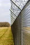 High security fence. Topped with barbed wire receding into distance Royalty Free Stock Images