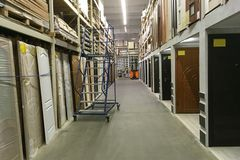 High shelves in the modern distribution storehouse store for the. Rows of high shelves in the modern distribution storehouse store for the sale of doors Royalty Free Stock Photos