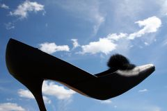 High on shoes. Black high heel shoe with sky background royalty free stock photography