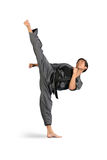 High Side Kick. Young Asian male performing a high side kick in a karate uniform wearing a black belt stock photos