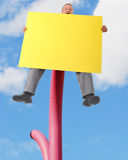 High Sign. A man sitting precariously high on a pole calling out and displaying a large sign left blank for your message Stock Photography