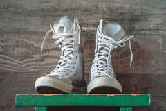 High sneakers with white laces. High youth sneakers with white laces stand on a green wooden shelf Royalty Free Stock Image