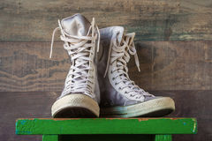 High sneakers with white laces. High youth sneakers with white laces stand on a green wooden shelf Royalty Free Stock Photo