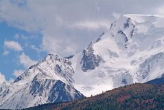 High snow covered mountain peak. With clouds background Royalty Free Stock Photo
