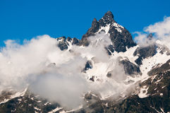 High, snow covered mountain peak. High, snow covered Alpine mountain peak partially covered by clouds Royalty Free Stock Image