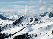 High snow covered mountains. A spectacular high mountain view overlooking a range of snow covered mountains Stock Images
