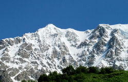 High snow mountain range above green valley Stock Images
