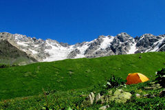 High snow mountain range above a small orange tent in green valley Stock Photography
