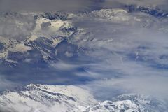 High snowy mountains, taken from an airplane, peaks are covered with fog and clouds, winter in the Himalayas. High snowy mountains, taken from an airplane, the Stock Photo