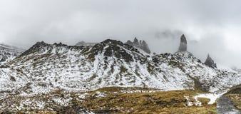 High snowy rocks hidden in a mist