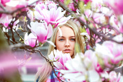 High society blond lady in pink blooming flowers looking at came Royalty Free Stock Image