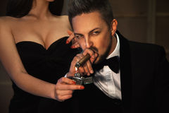 High society Portrait of man smoking cigar and lady with a cigar Royalty Free Stock Photo