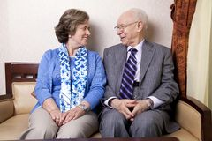 Happy Senior Couple. A high society senior couple (he's in his 80's, she's in her late 60's) sitting on a sofa looking at each other with very much love and joy Royalty Free Stock Photography