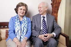 Happy Elderly Couple. A high society senior couple (he's in his 80's, she's in her late 60's) sitting on a sofa. He's smiling and looking at her, and she's Royalty Free Stock Photo