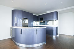 High spec designer kitchen in metal blue. Ultra modern designer kitchen with modern appliances in metal blue and gray Stock Photography