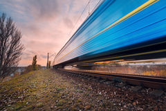 High speed blue passenger train on railroad track in motion Stock Photos