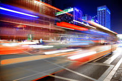 High speed and blurred bus light trails in downtown nightscape Stock Photography