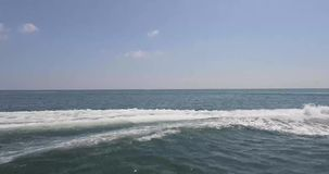 A high-speed and sea. A high-speed bright boat at high speed sail past the camera leaving a foamy footprint. Passenger boat is delighted stock video footage