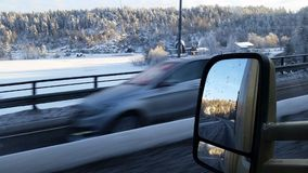 High speed car passing, rear view in mirror, and view over frozen lake Stock Photo