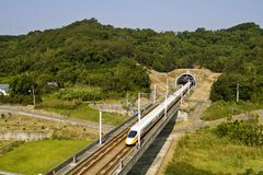 High-speed commuter train. High speed train driving across tunnel with mountain scenery Stock Images