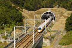 High-speed commuter train. High speed train driving across tunnel with mountain scenery Stock Image