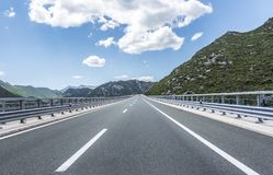 High-speed country road among the mountains. Royalty Free Stock Images