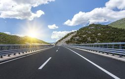 High-speed country road among the mountains. Stock Photos