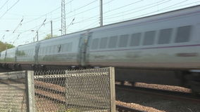 High speed electric train. High speed electric train pass a level crossing then the barriers go up.   Video shot on the main London to Scotland railway line stock footage