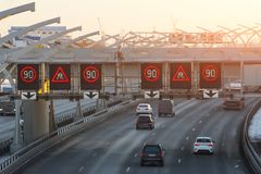 High-speed highway with traffic cars and speed limit signs and a slippery road warning. royalty free stock photos